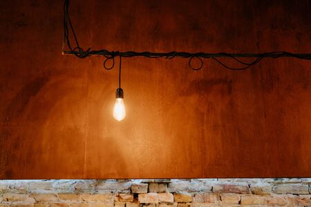 Lighting Edison Lightbulb with Electrical Cord on Rust Metallic and Old Brick Wall Background Copyspace. Industrial Pendant Lamp. Loft Retro Grunge Style Interior. Classical Illumination Device