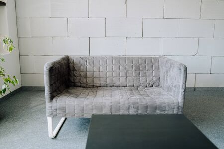 Sofa Modern Textile Grey Upholstery Room Element with Foam Brick Wall on Background Copy Space. Elegant Fabric Couch and Black Table on Gray Carpet Covering Floor. Office Stylish Interior Archivio Fotografico
