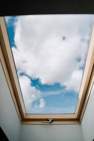Roof Skylight Window and Blue Sky with Clouds Copy Space Photography. Attic Floor Ceiling Modern Room Element with Beautiful View and Day Light. Mansard Glass with Wooden Frame and Handle