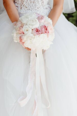 Bride Holding Wedding Bouquet of Beautiful Flowers White and Rose Roses Decorated Ribbons Photo. Romantic Floral Traditional Decorative Accessory. Fashion Stylish Bridal Posy Photography