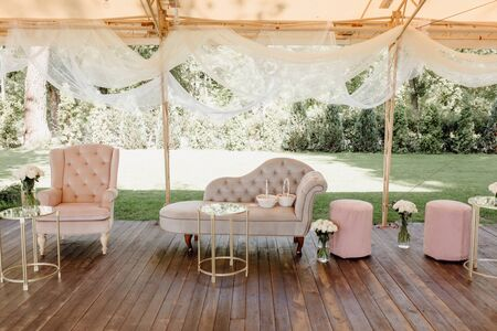 Couch, Chair near Tables and Flowers Bouquets near Taburet Standing on Wooden Flooring under Canopy Decorated White Curtains. Relaxation Lounge Zone. Green Grass and Trees on Background