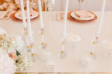 Kaarsen Atanding in Crystal decoratieve kandelaars en bloemboeket op eettafel horizontale fotografie. Servet op borden voor heerlijke maaltijd en wijnglazen op onscherpe achtergrond Stockfoto