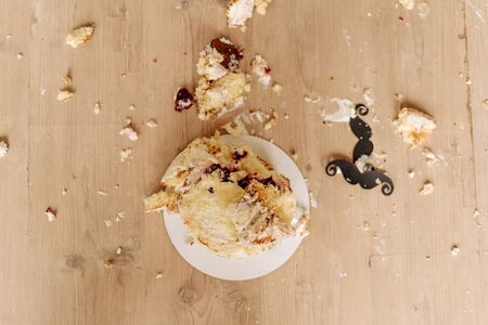 Smashed First Birthday Cake on Floor Flat Lay Photo. Destroyed Delicious Creamy Celebrate Biscuit Dessert Heaped Mess and Paper Moustache Decoration. Remains Pieces Horizontal Photography Foto de archivo