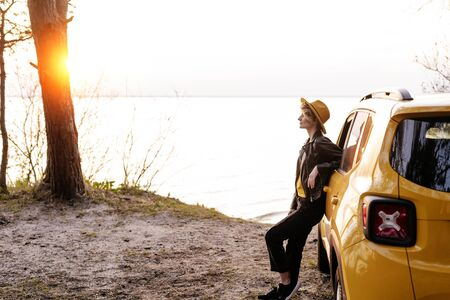 Young Woman Lean against Car at Sea Shore Sunset