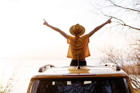 Woman Spread Arms Widely at Car Sunroof Back View