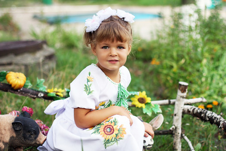 animal figurines: little girl with blond hair and white dress sitting in the park and played with animal figurines Stock Photo