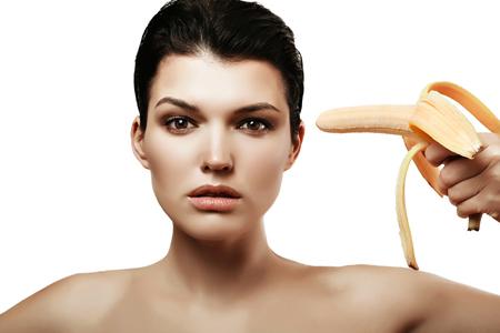 relaciones sexuales: La muchacha bonita con un plátano en su mano. las relaciones sexuales sin protección. Anticoncepción.