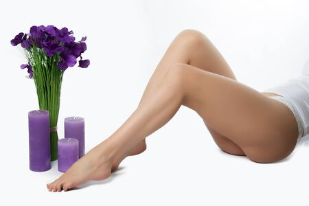 feet naked: Beautiful slender female legs with silky skin, hair removal, depilation, shugaring. Bouquet of flowers, candles, underwear.