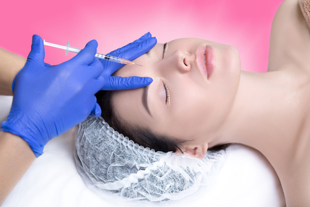 beautiful and well-groomed girl is given injections of youth, wrinkle smoothing, hyaluronic acid, botox, facial skin care