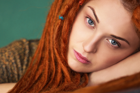 beautiful and intelligent girl with red dreadlocks and blue eyes is sad, close-up portrait