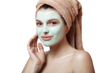 Close-up portrait of a beautiful and well-groomed woman in a towel and with a mask on her face on a white background, isolated. Face and body care. Spa, beauty treatments.