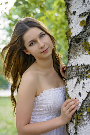 european white birch: the beautiful girl with long hair embraces a birch