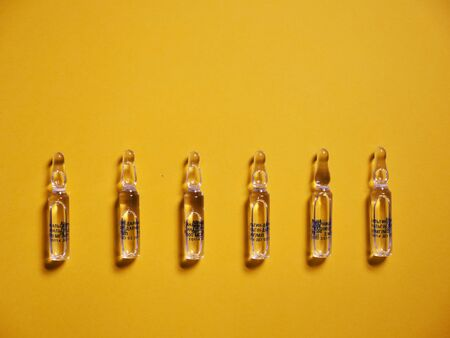 Ampoule on a yellow background for the treatment of Coronavirus Covid19 Reklamní fotografie