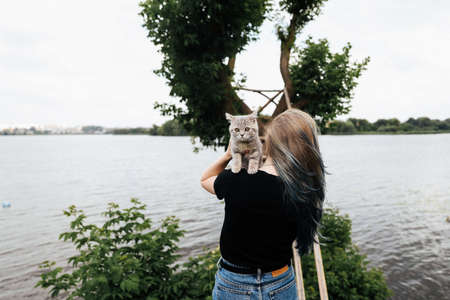A girl with blue hair stands with her back and holds a three month old Scottish Straight kitten outside in the summer near a tree. The cat looks at the camera.. High quality photo