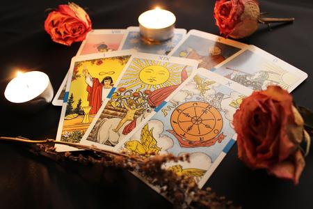 Tarot cards, candles lights, dried rose buds and sprig of wormwood on black satin background Redakční