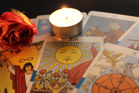 Tarot cards, candle light, dried rose bud on black background Stok Fotoğraf