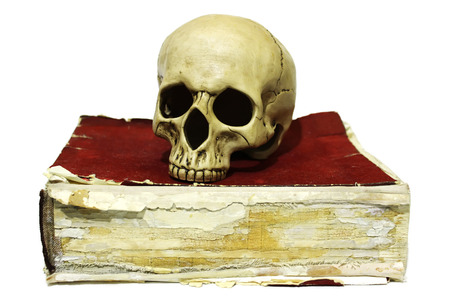 Human skull on old book isolated on white background