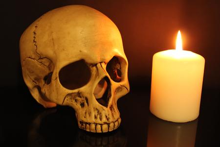 Human skull and white burning candle on black background