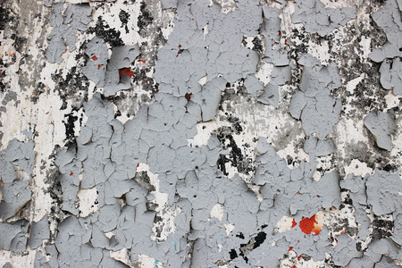 Old shabby cracked wall with old layers of gray paint 免版税图像