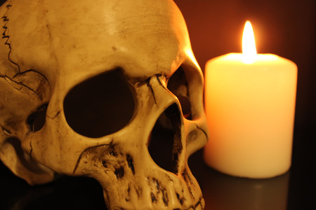 Human skull and white burning candle 免版税图像