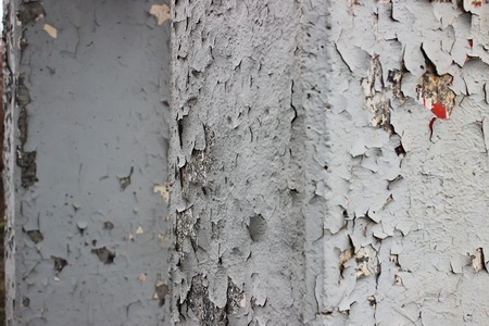 Two old shabby cracked pillars with layers of gray paint