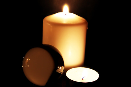Glass ball and burning candles in the dark 免版税图像