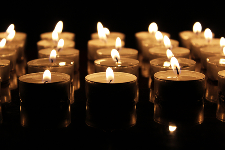 Many burning candles in the dark