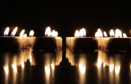 Burning candles on reflective surface 免版税图像