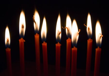 Many burning red thin wax candles in the dark