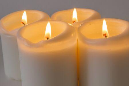 White burning candles close up