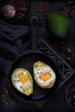 cast iron pan: baked avocado with egg and brie in a cast iron pan on a dark background Stock Photo