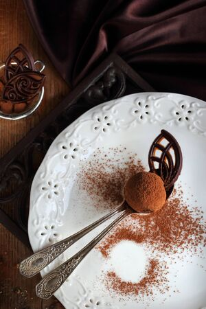 truffe blanche: homemade chocolate truffle dusted with cocoa in two spoons on a white plate
