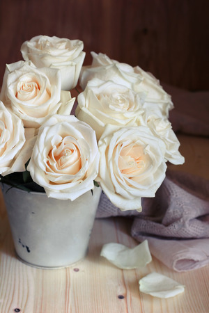 rosas blancas: Bouquet of white roses in a bucket on a wooden background. Taken with natural light. Foto de archivo