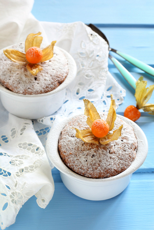 winter cherry: two muffins in white ceramic forms sprinkled with powdered sugar decorated winter cherry on a blue background