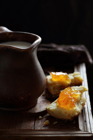 anointed: Scones with orange marmalade and a jug of milk against backlight. Taken with natural light. Stock Photo