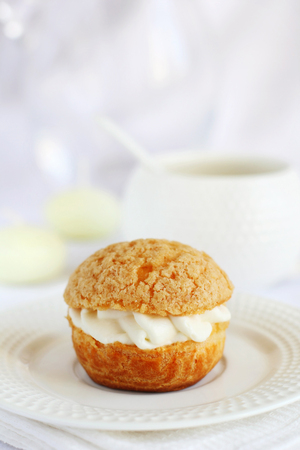 profiterole: one profiterole stuffed with cream on a white background, shot with natural light