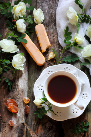 black boards: cup of black tea and rosehip flowers on wooden boards Stock Photo