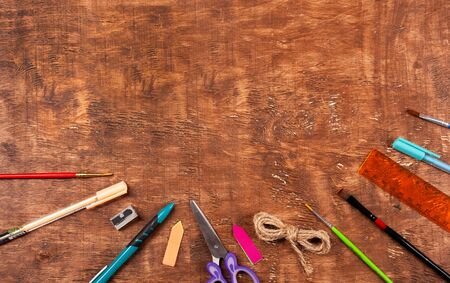 Schoolboy stationery on wooden natural brown background.