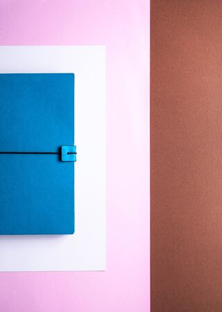 lifestyle for business stationery and education concept with a closeup image of a vintage azure notepad with blank pages or copy space on a background of sweet pastel pink tones Stock fotó