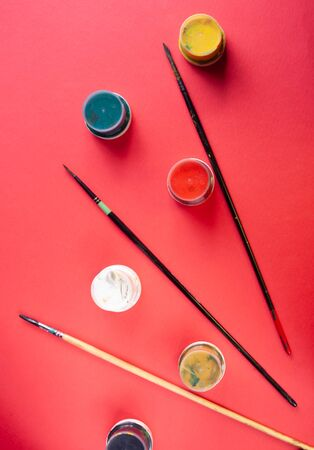 Paint brushes and paints on a red background