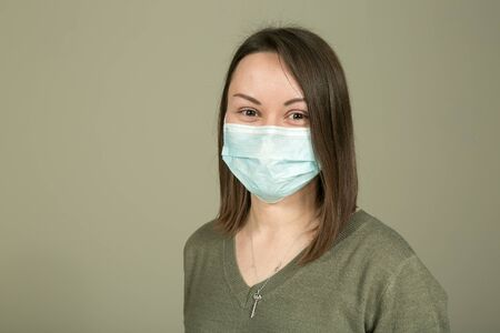 During quarantine and isolation, the mask does not interfere with full communication. The emotions of a young and beautiful woman in a mask on a green background while communicating with other people. Stock Photo