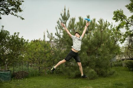 The joy of a young man in the nature after quarantine. The boy jumps for joy and throws out unnecessary medical masks and gloves.
