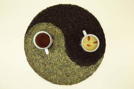 Sign Yin Yang with tea. Used Chinese black tea and green Lundzin. Black tea and Lundzin with goji are brewed in cups. Healthy eating concept.