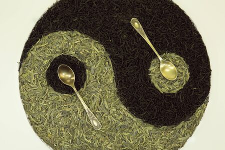 Sign Yin Yang with tea. Used Chinese black tea, green Lundzin and two spoons. Healthy eating concept.