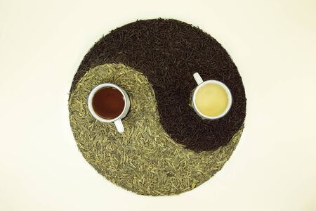 Sign Yin Yang with tea. Used Chinese black tea and green Lundzin. Black tea and Lundzin are brewed in cups. Healthy eating concept.