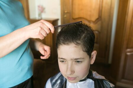 Home haircut during quarantine. The best master is mother's hands, scissors and a trimmer. Stock Photo