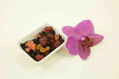 Chinese tea. Chinese fruit tea with hibiscus. Orchid flower. Fruit tea with hibiscus isolated in a white bowl on a white background.