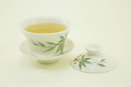 Chinese green tea. Ginseng tea Xiao Zhong. Green tea in a beautiful traditional oriental cup with saucer. Isolated in a white bowl on a white background.