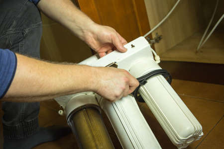 The master replaces dirty filters in the home water purification system. Human hands, filter, membrane.
