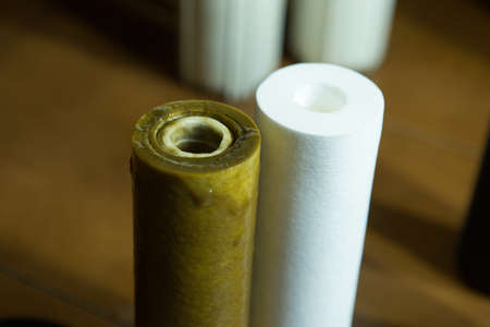 Changing filters in your home water purification system. Dirty and clean filter 5 microns.